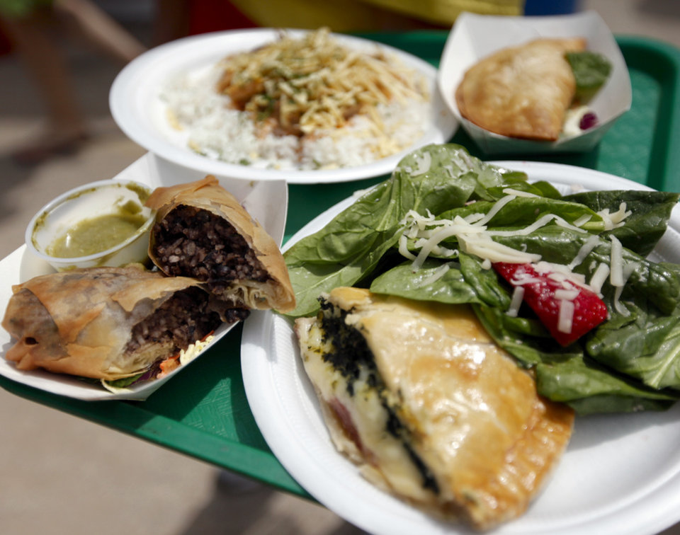 Photo - Clockwise from lower right, Braslilan Pie with Salad, Feijoada Rolinho (Pork Egg Roll), Chicken Stroganoff and Pastel (Shrimp Empanada) from the Cafe do Brasil & Flamenco Fantasico of the Everything Goes Dance Studio booth are pictured on International Food Row during the Festival of the Arts in downtown Oklahoma City, Wednesday, April 25, 2012. Photo by Nate Billings, The Oklahoman
