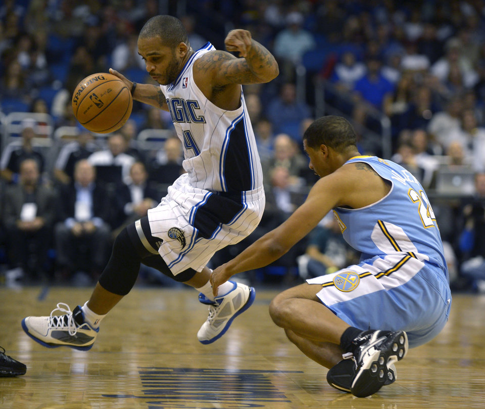 Orlando Magic guard Jameer Nelson, left, gains control of a loose ball in front of Denver Nuggets guard Andre Miller during the first half of an NBA basketball game in Orlando, Fla., Friday, Nov. 2, 2012. (AP Photo/Phelan M. Ebenhack)