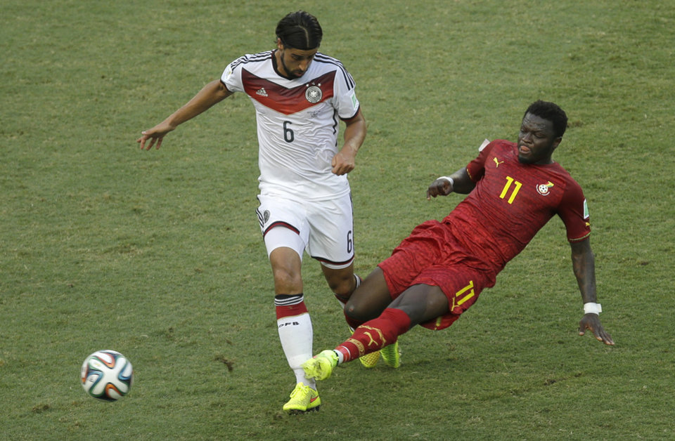 Photo - Germany's Sami Khedira, left, and Ghana's Sulley Muntari challenge for the ball during the group G World Cup soccer match between Germany and Ghana at the Arena Castelao in Fortaleza, Brazil, Saturday, June 21, 2014. (AP Photo/Themba Hadebe)
