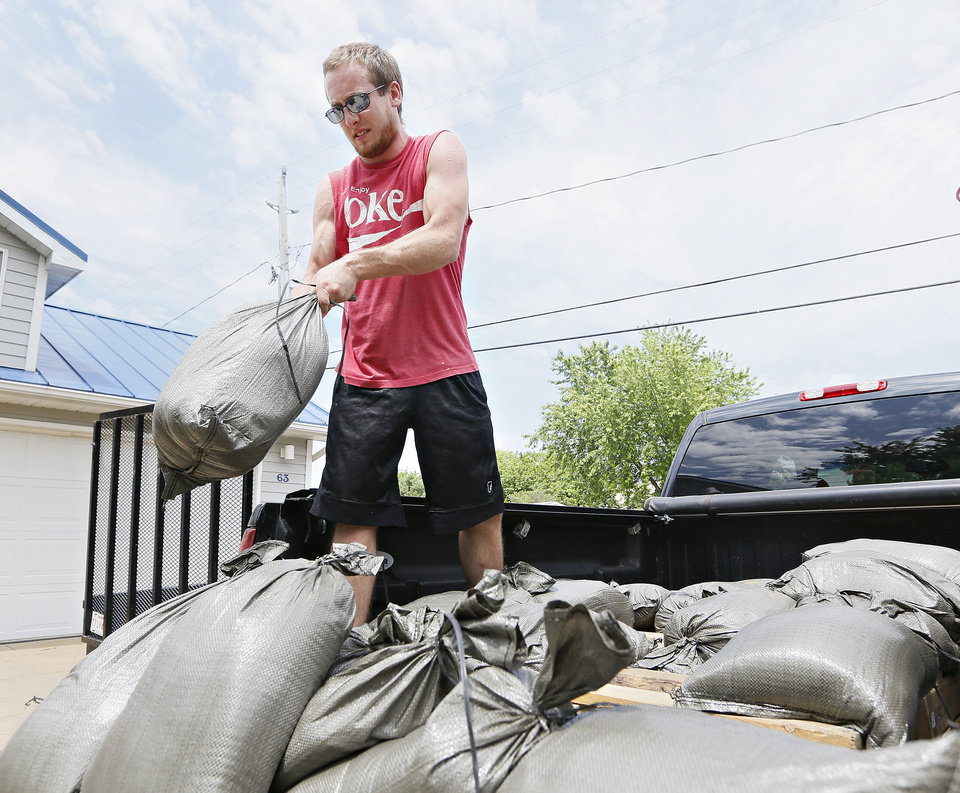 Photo - Colby Grant, of Jefferson, tosses sand bags from a truck bed as he helps his father, Dennis Johnson, prepare his home for flooding in McCook Lake, S.D., on Thursday, June 19, 2014. People along the river were working to battle record flooding. (AP Photo/Sioux City Journal, Dawn J. Sagert)
