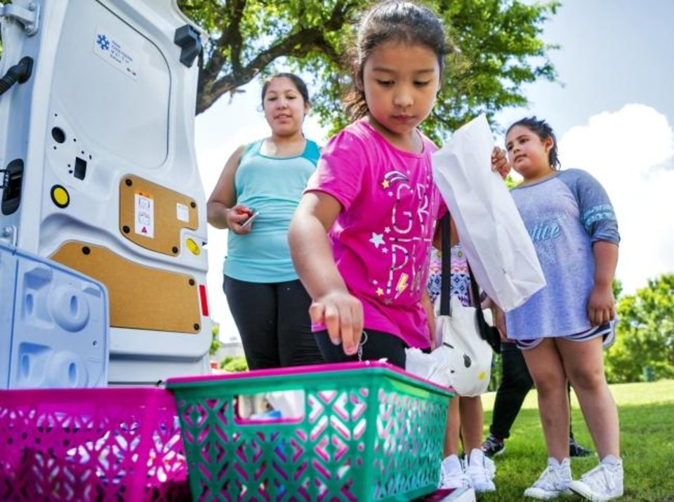 Photo -  Yoselin Ramirez, 6,  fills her lunch bag during the  Summer Feeding Program from Oklahoma City Public Schools at Wiley Post Park. [Chris Landsberger/The Oklahoman]