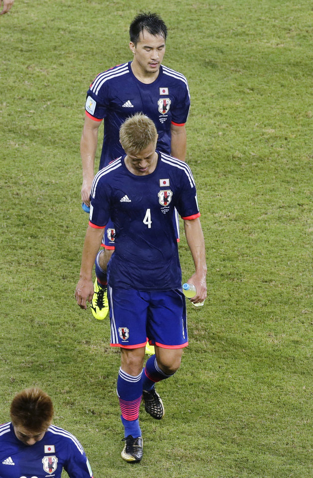 Photo - Japan's Keisuke Honda, front, and Shinji Okazaki leave the pitch after a draw in the group C World Cup soccer match between Japan and Greece at the Arena das Dunas in Natal, Brazil, Thursday, June 19, 2014. (AP Photo/Hassan Ammar)