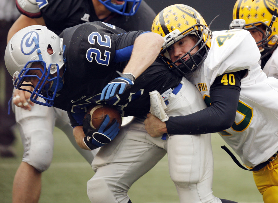 Seth John (40) of Lawton MacArthur tackles Luke Davis (22) of Guthrie during the Class 5A high school football state championship game between Guthrie and Lawton MacArthur at Boone Pickens Stadium in Stillwater, Okla., Friday, Dec. 2, 2011. Photo by Nate Billings, The Oklahoman