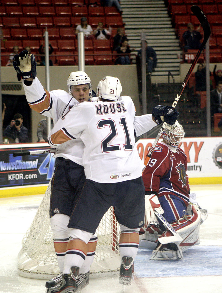 Photo - Oklahoma City's Tanner House (21) and Antti Tyrvainen celebrate a goal in front of Hamilton goalie Peter Delmas during the AHL hockey game between the Oklahoma City Barons and the Hamilton Bulldogs at the Cox Convention Center in Oklahoma City, Tuesday, April 3, 2012. Photo by Sarah Phipps, The Oklahoman