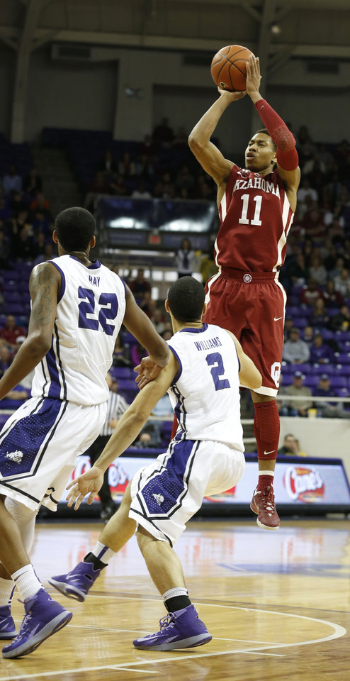 Photo - TCU guards Jarvis Ray (22) and Michael Williams (2) watch as Oklahoma guard Isaiah Cousins (11) takes a shot in the first half of an NCAA basketball game Saturday, March 8, 2014, in Fort Worth, Texas. Oklahoma won 97-67. (AP Photo/Sharon Ellman)