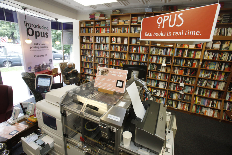 Photo -   In this June 5, 2012, photo, a customer reads a book by the Espresso Book Machine, known as Opus, at Politics and Prose bookstore in Washington. Self-publishing has been made easier since the machine by On Demand Books debuted in 2006. The machine also can makes copies of out-of-print editions. The first machine was installed briefly at the World Bank's bookstore. Through a partnership with Xerox, the company now has machines in about 70 bookstores and libraries across the world including London; Tokyo; Amsterdam; Abu Dhabi, United Arab Emirates; Melbourne, Australia; and Alexandria, Egypt. (AP Photo/Jacquelyn Martin)