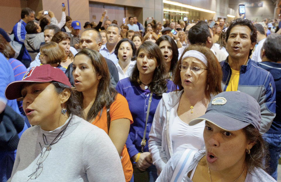Photo -   Venezuelan citizens living in the United States including Susana Guillen form Atlanta, bottom left, and Rosabla Cabello from Jackson, Miss. sing the Venezuelan national anthem as they wait to vote at the New Orleans Ernest Morial Convention Center, in New Orleans, Sunday, Oct. 7, 2012. Hundreds of Venezuelans living in the U.S. streamed into New Orleans on Sunday to cast ballots in the presidential election in their homeland, many of them determined to end the 13-year reign of Hugo Chavez. With the country's consulate in Miami closed, thousands of Venezuelans traveled by bus, car and plane to cast their votes at the consulate in New Orleans. (AP Photo/Matthew Hinton)