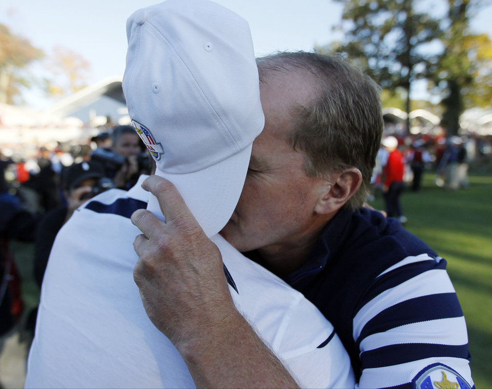 USA's Steve Stricker covers his face as he hugs Europe's Martin Kaymer after a singles match at the Ryder Cup PGA golf tournament Sunday, Sept. 30, 2012, at the Medinah Country Club in Medinah, Ill. (AP Photo/Charles Rex Arbogast)  ORG XMIT: PGA199