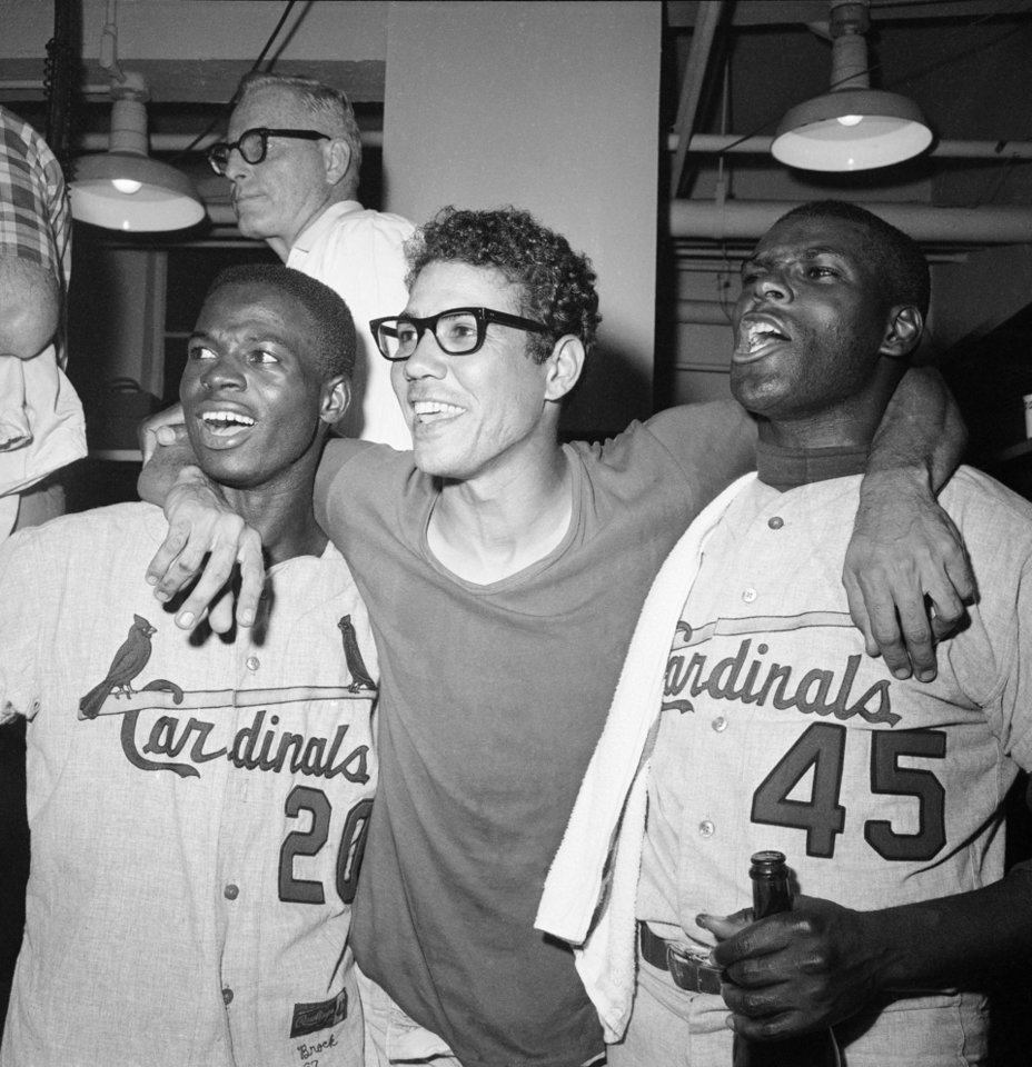Photo - FILE - In this Oct. 12, 1967, file photo, St. Louis Cardinals Lou Brock, left, Julian Javier, center, and Bob Gibson celebrate defeating the Boston Red Sox 7-2 to win the World Series, in Boston. The World Series starts in Boston on Wednesday, Oct. 23, 2013, when the Red Sox will play the Cardinals in a rematch of the 1946, 1967 and 2004 Series. (AP Photo/File)