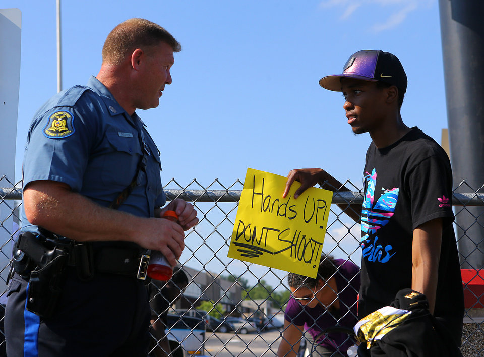 Photo - In an effort to foster some good will Missouri State Higway Patrol trooper D. Reuter chats with protester Robert Clark along West Florissant Avenue on Tuesday, Aug. 19, 2014, in Ferguson, Mo.   The city of Ferguson, Missouri, says it working hard to better connect with the community and learn from the