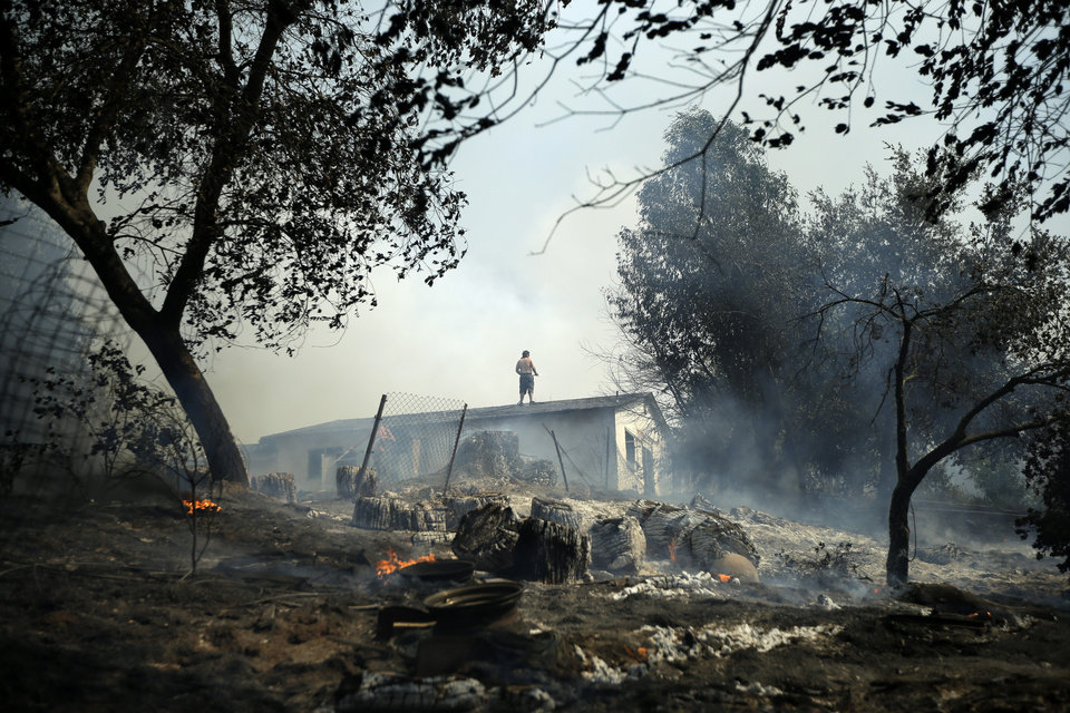 Photo - Jeff Brown waters the roof of his home as vegetation smolders during a wildfire, Thursday, May 15, 2014, in Escondido, Calif. One of the nine fires burning in San Diego County suddenly flared Thursday afternoon and burned close to homes, trigging thousands of new evacuation orders.(AP Photo/Gregory Bull)