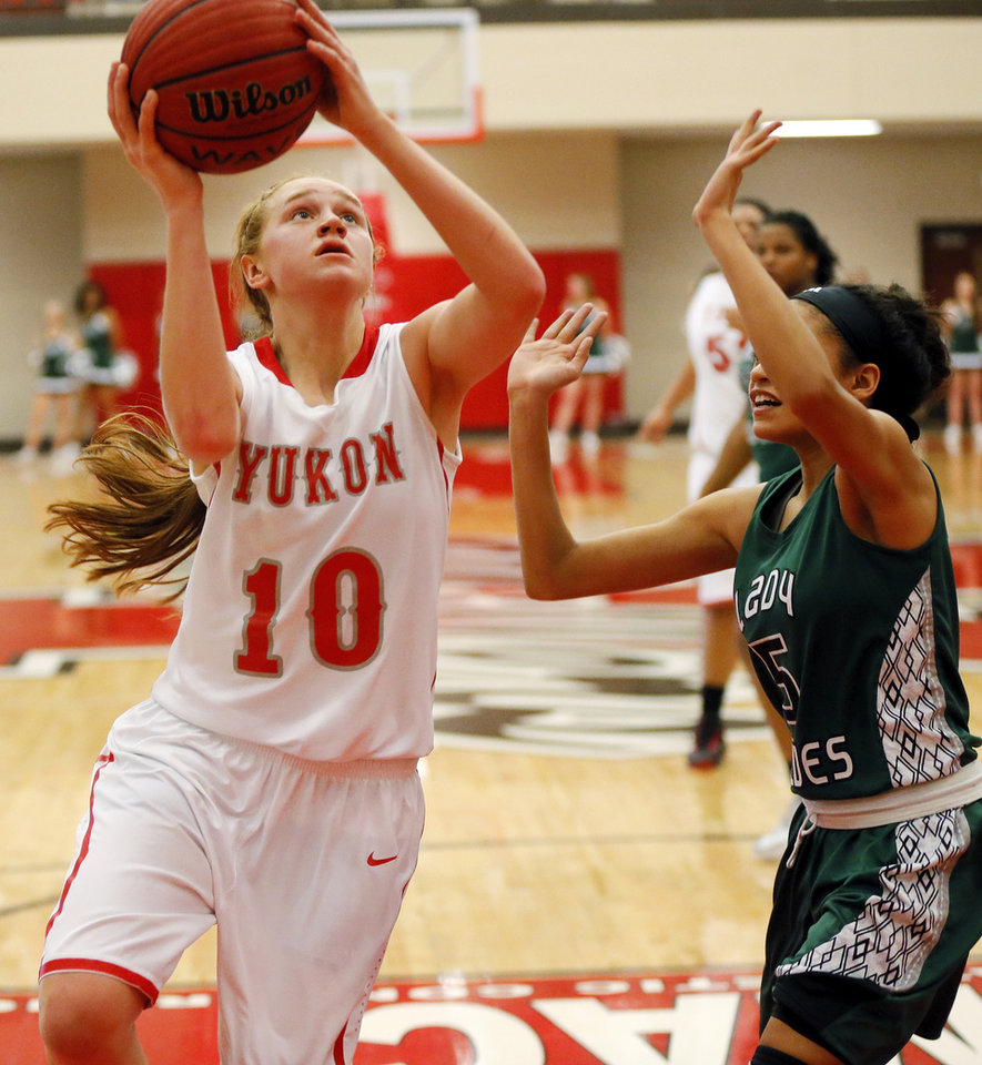 Photo - Yukon's Audrey Hayes, left shoots against Edmond Santa Fe's Summer Jones during a game Friday. Photo by Nate Billings, The Oklahoman