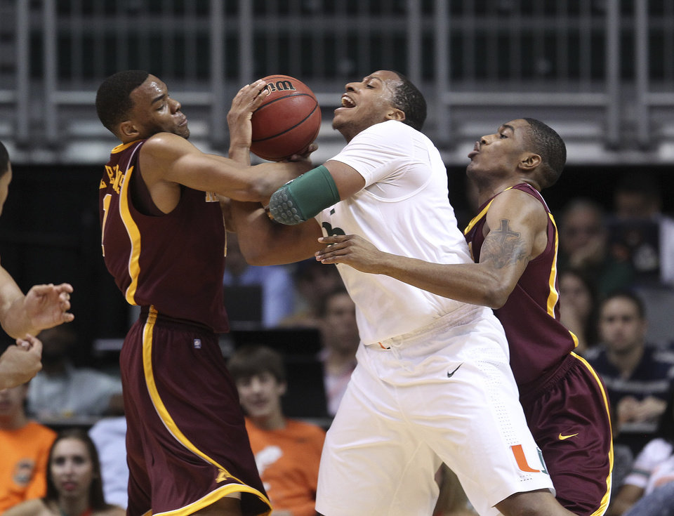 Photo -   Miami's Kenny Kadji (35) fights Minnesota's Andre Hollins, left, and Andre Ingram for the ball during the first half of the second-round of the NIT tournament NCAA college basketball game in Coral Gables, Fla., Monday, March 19, 2012. (AP Photo/J Pat Carter)