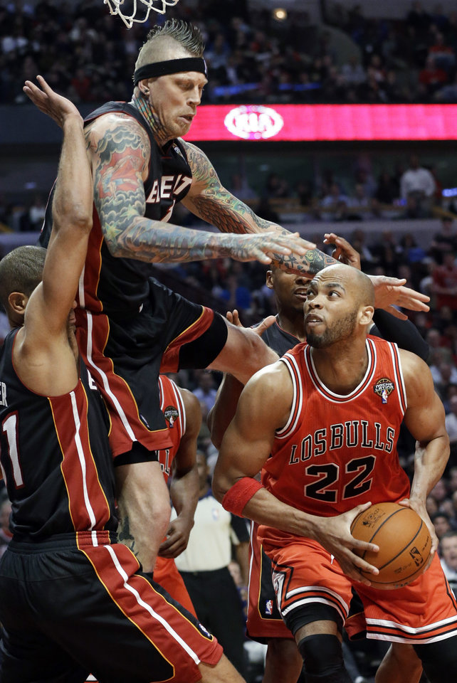 Photo - Chicago Bulls forward Taj Gibson (22) looks to the basket against Miami Heat forward Chris Andersen, top, and forward Shane Battier during the second half of an NBA basketball game in Chicago on Wednesday, March 27, 2013. The Bulls won 101-97, ending the Heat's 27-game winning streak. (AP Photo/Nam Y. Huh)