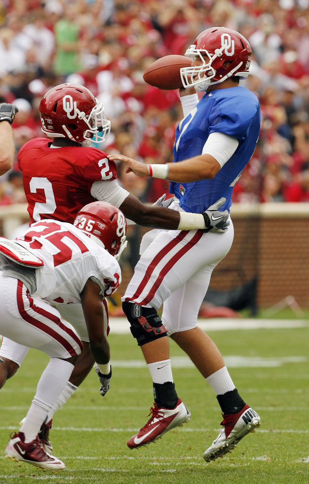 Photo - Quarterback Blake Bell (10) is pressured by Julian Wilson (2) during the University of Oklahoma (OU) football team's annual Red and White Game at Gaylord Family/Oklahoma Memorial Stadium on Saturday, April 14, 2012, in Norman, Okla.  Photo by Steve Sisney, The Oklahoman