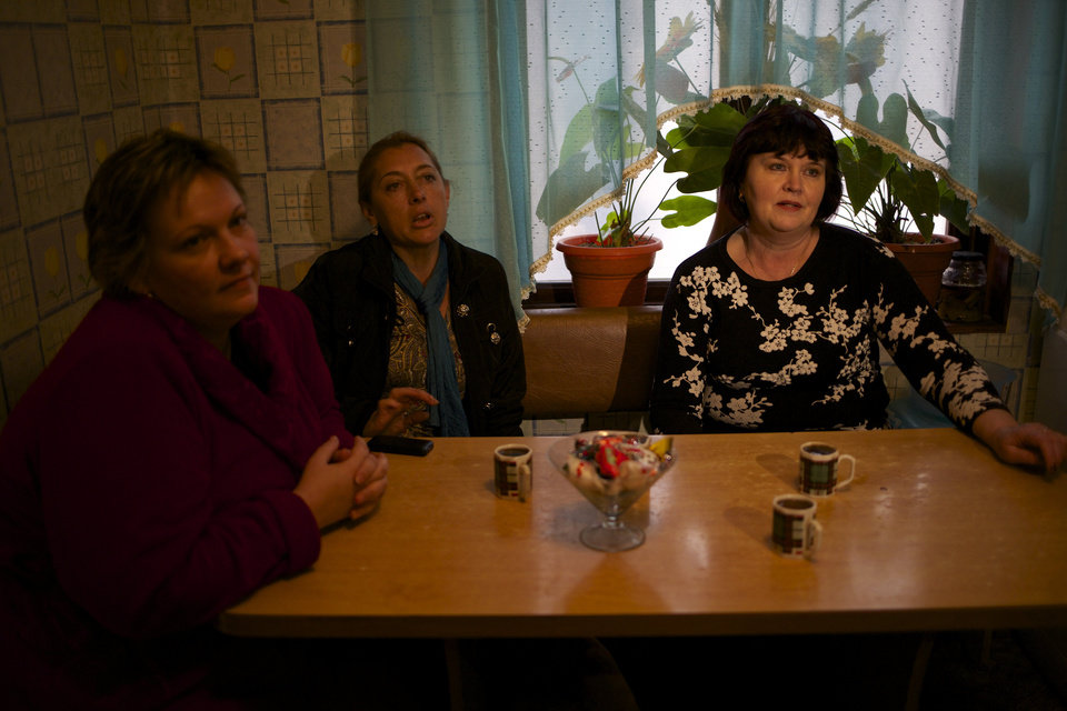 Photo - In this picture taken on Wednesday, Nov. 27, 2013, Alexandra Krivchenko, left, Nadezhda Kurovskaya, center, Irina Kharchenko, right, residents of 5a Akatsiy, street drink tea in the village of Vesyoloye outside Sochi, Russia. As the Winter Games are getting closer, many Sochi residents are complaining that their living conditions only got worse and that authorities are deaf to their grievances. (AP Photo/Alexander Zemlianichenko)