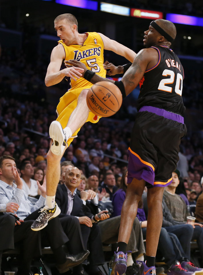 Photo - Los Angeles Lakers' Steve Blake, left, tries to save a ball from going out of bounds as Phoenix Suns' Jermaine O'Neal, right, defends during the first half of an NBA basketball game, Tuesday, Feb. 12, 2013, in Los Angeles. (AP Photo/Danny Moloshok)