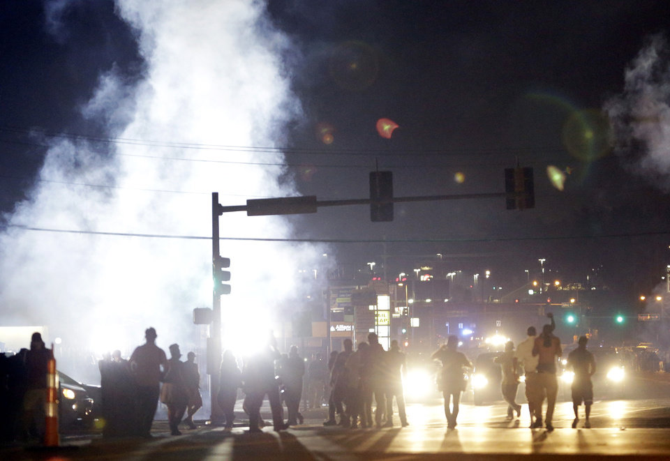 Photo - FILE - In this Monday, Aug. 18, 2014 file photo, people stand near a cloud of tear gas in Ferguson, Mo. during protests for the Aug. 9 shooting of unarmed black 18-year-old Michael Brown by a white police officer. The U.S. government agreed to a police request to shut down several miles of airspace surrounding Ferguson, even though authorities said their purpose was to keep media helicopters away during protests in August, according to recordings of air traffic control conversations obtained by The Associated Press. (AP Photo/Jeff Roberson)