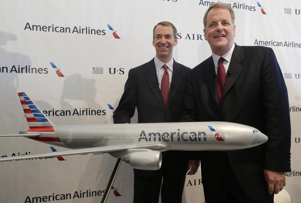 FILE - In this Feb. 14, 2013 file photo, U.S. Airways CEO Doug Parker, right, and American Airlines CEO Tom Horton pose after a news conference at DFW International Airport Thursday, Feb. 14, 2013, in Grapevine, Texas. It wasn't an easy fight, but by the end of this year the 51-year-old Parker will be at the helm of a combined American and US Airways, the world's largest airline. Horton, also 51, will step aside, getting $19.9 million in cash and stock as well as a lifetime of free first class flights, excluding taxes, on American for himself and his wife. Horton will serve as chairman for about a year before stepping down. (AP Photo/LM Otero, File)