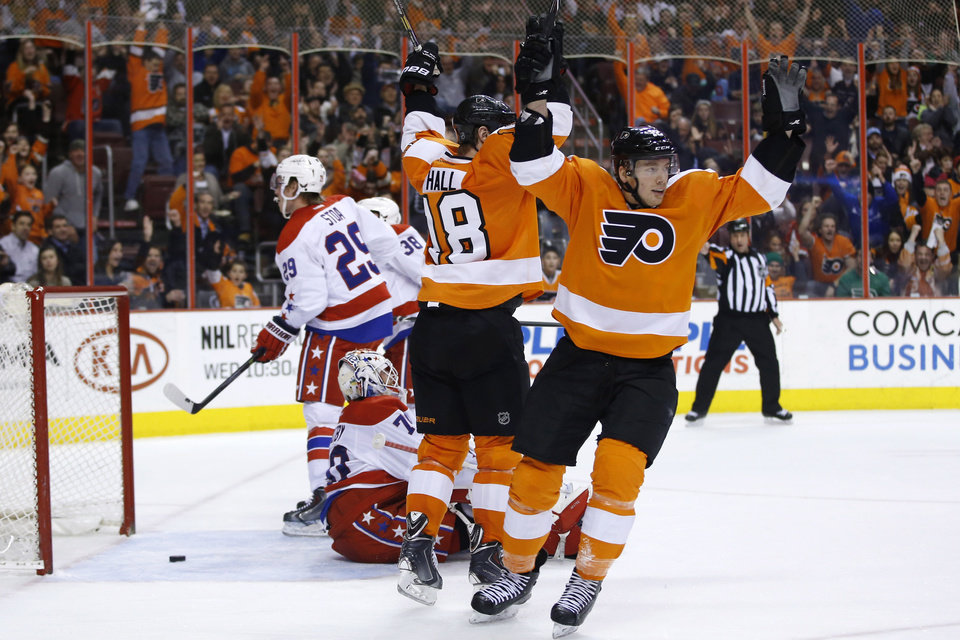 Photo - Philadelphia Flyers' Michael Raffl, right, of Austria, and Adam Hall, center, celebrate after Raffl's goal during the second period of an NHL hockey game against the Washington Capitals, Wednesday, March 5, 2014, in Philadelphia. (AP Photo/Matt Slocum)
