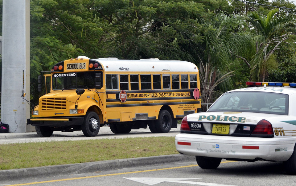 Police investigate the scene of a shooting on a school bus in Homestead, Fla., near Miami, Tuesday, Nov. 20, 2012. Miami-Dade police say a 13-year-old girl has died after she was shot by another student on the school bus in Homestead. A male student is in custody and police spokesman Alvaro Zabaleta says investigators are talking to him. A gun was also recovered at the scene. (AP Photo/El Nuevo Herald,Gaston De Cardenas) MAGS OUT