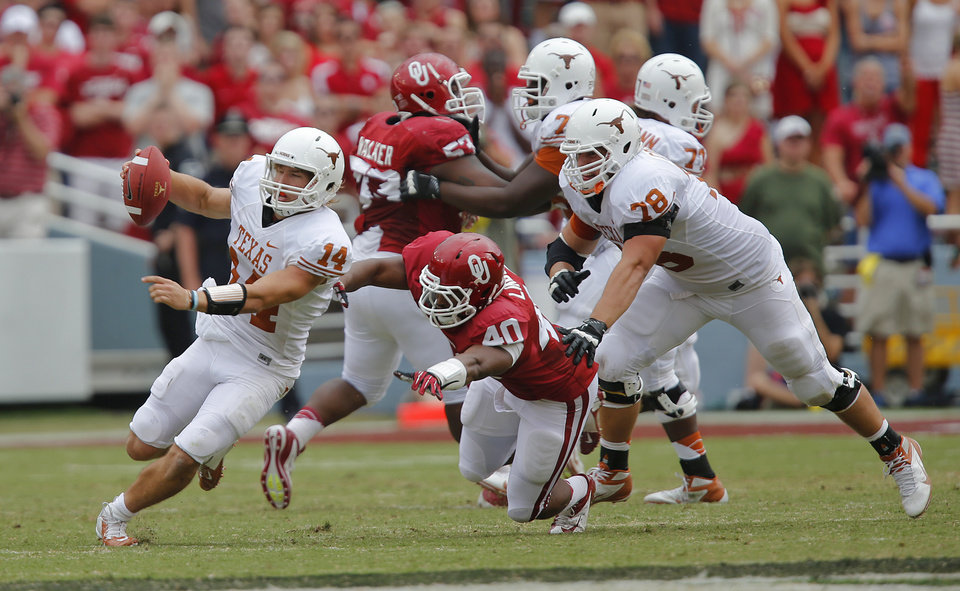 Photo - UT's David Ash (14) escapes OU's P.L. Lindley (40) during the Red River Rivalry college football game between the University of Oklahoma (OU) and the University of Texas (UT) at the Cotton Bowl in Dallas, Saturday, Oct. 13, 2012. Photo by Chris Landsberger, The Oklahoman
