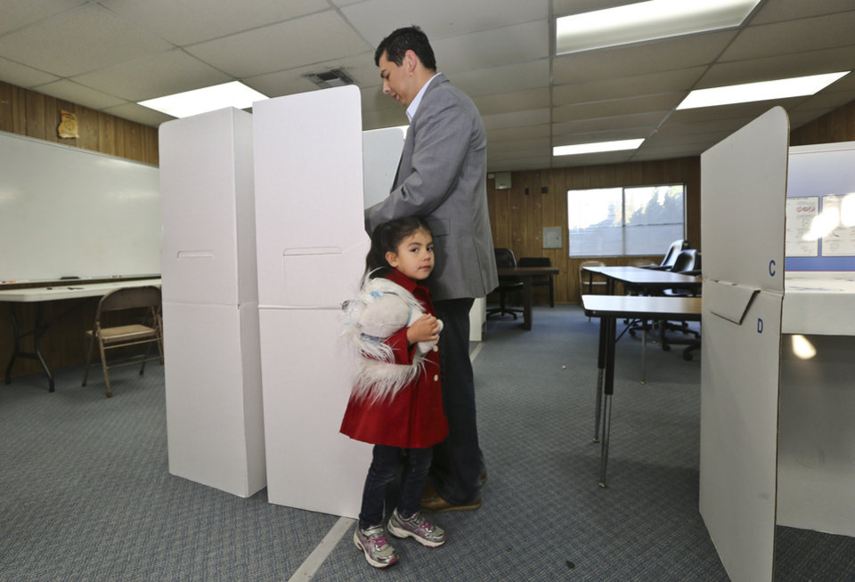 Photo - San Diego mayoral candidate David Alvarez cast his ballot as a his daughter, Izel, holds onto his leg at a polling location in the Logan Heights neighborhood where Alvarez grew up and still lives Tuesday, Feb. 11, 2014 in San Diego. (AP Photo/Lenny Ignelzi)