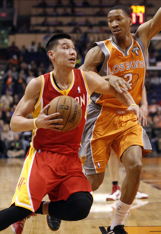 Houston Rockets guard Jeremy Lin, left, drives to the basket past Phoenix Suns forward Wesely Johnson, right, during the first half of an NBA basketball game on Saturday, March 9, 2013, in Phoenix. (AP Photo/Paul Connors)