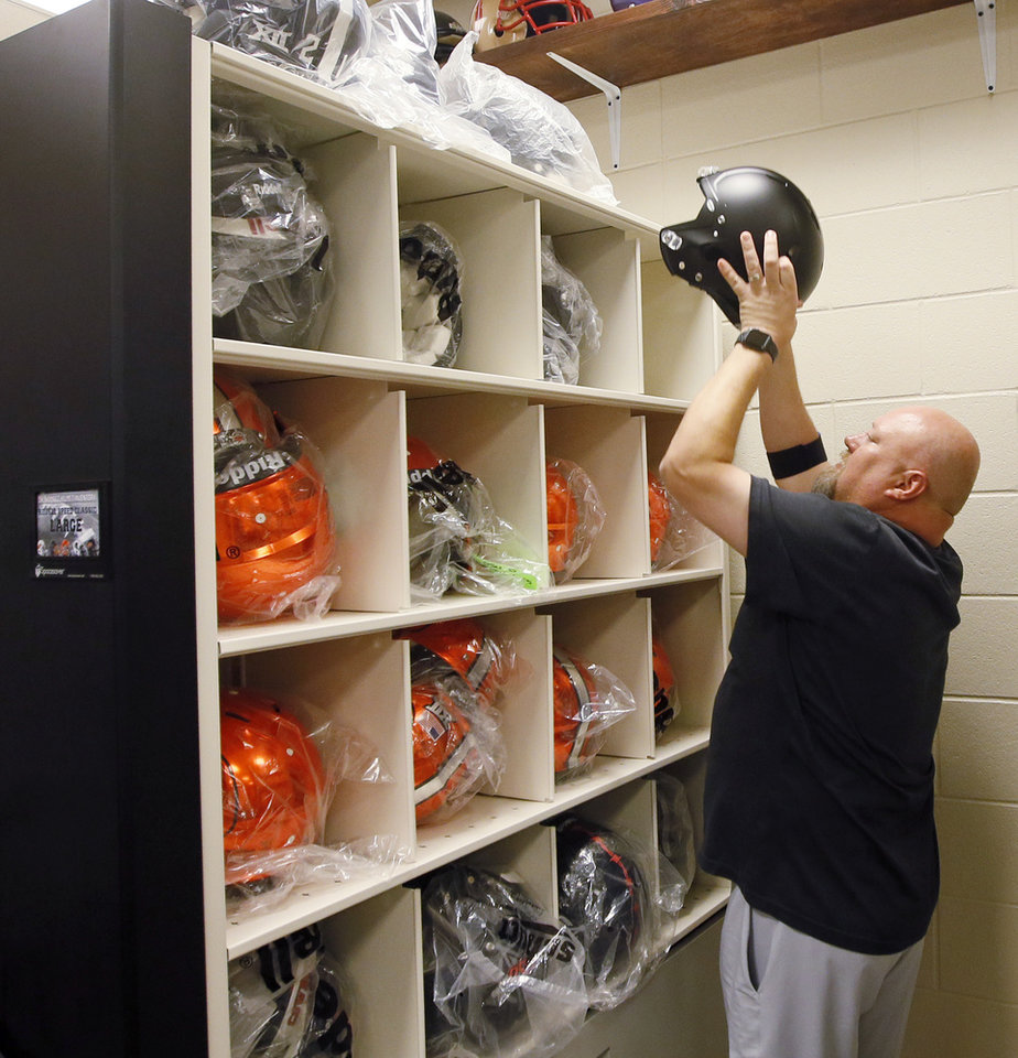 Photo -  Len Magby, OSU assistant director of football equipment, takes a black helmet off a shelf while preparing new game helmets for players who don't have them yet at Boone Pickens Stadium. [PHOTO BY NATE BILLINGS, THE OKLAHOMAN]