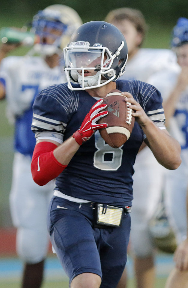Photo - Shawnee quarterback John Jacobs works the offense during a high school football scrimmage at Choctaw High School, Friday, August 22, 2014. Photo by Doug Hoke, The Oklahoman