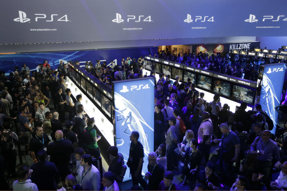 Photo - FILE - In this June 11, 2013 file photo, show attendees play video games on the new Sony PlayStation 4 at the Sony booth during the Electronic Entertainment Expo, in Los Angeles. With the launch of the Xbox One, PlayStation 4 and Wii U in the video game industry's rearview mirror, the spotlight at the Electronic Entertainment Expo, held June 10-12, 2014, is expected to shift back to games. From online-only titles to virtual reality experiences, about 200 exhibitors will hype their latest software in hopes of driving away from E3 with The Next Big Thing. (AP Photo/Jae C. Hong, file)