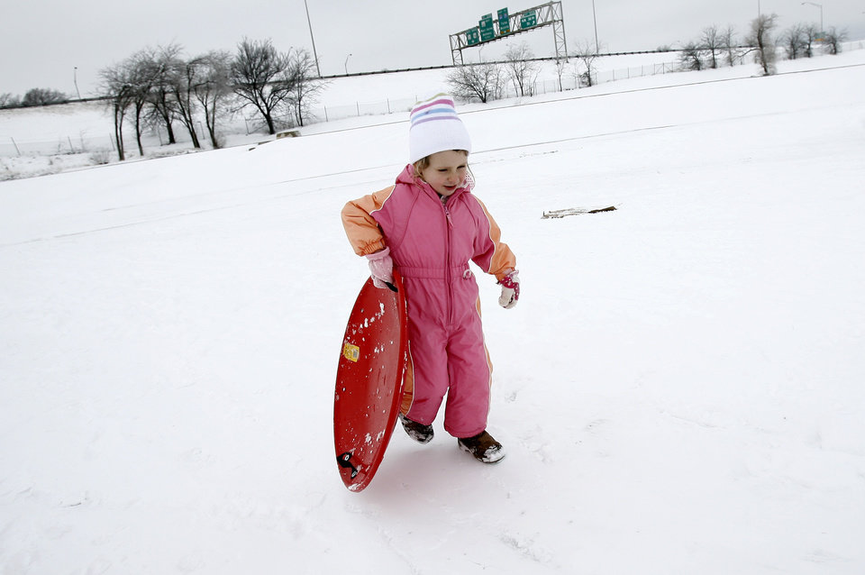 Photo - Alaina Clifton, 4, of Oklahoma City carries her sled up a hill at Will Rogers Park, Saturday, Jan. 30, 2010, in Oklahoma City. Photo by Sarah Phipps, The Oklahoman