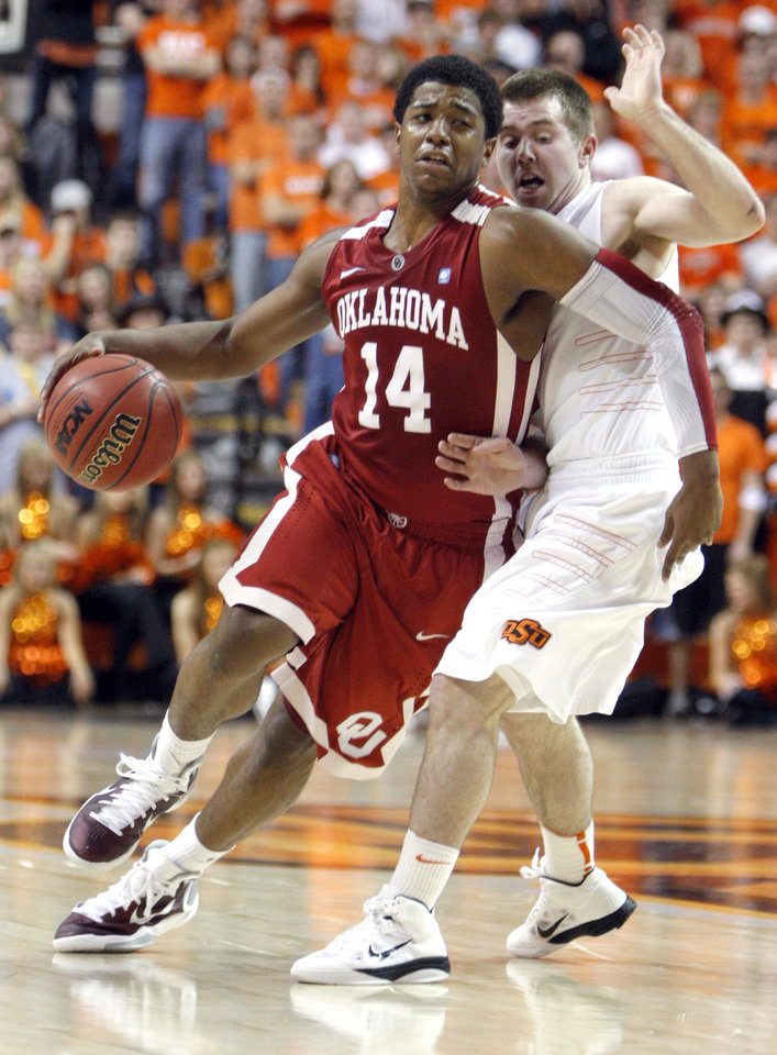 Photo - Oklahoma's Carl Blair Jr. (14) tries to get past Oklahoma State's Keiton Page (12) during the Bedlam men's college basketball game between the University of Oklahoma Sooners and Oklahoma State University Cowboys at Gallagher-Iba Arena in Stillwater, Okla., Saturday, February, 5, 2011. Photo by Sarah Phipps, The Oklahoman