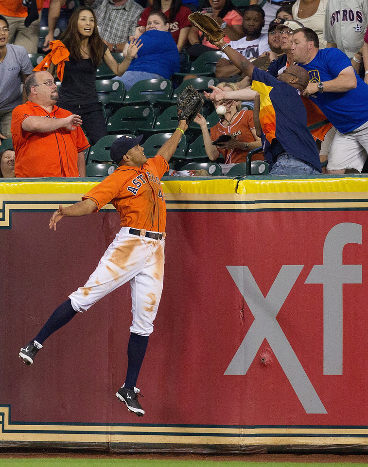 Houston Astros' Justin Maxwell leaps but cannot make a catch on a home run hit by Seattle Mariners' Brad Miller in the eighth inning of a baseball game Friday, July 19, 2013, in Houston. (AP Photo/Bob Levey)