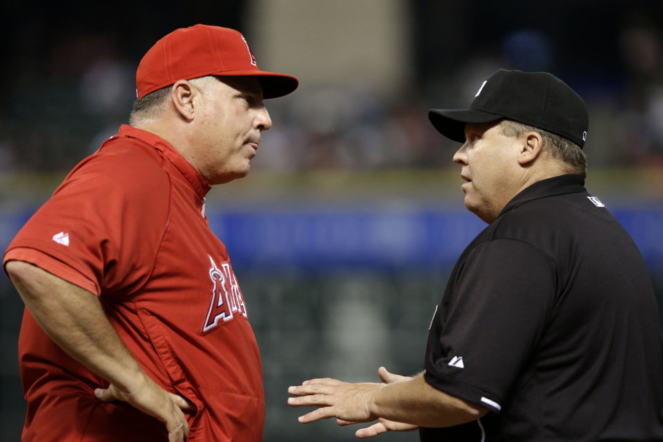 Photo - Los Angeles Angels manager Mike Scioscia, left, argues a close play at first base with umpire Fieldin Culbreth in the second inning of a baseball game against the Houston Astros, Thursday, May 9, 2013, in Houston. (AP Photo/Pat Sullivan)