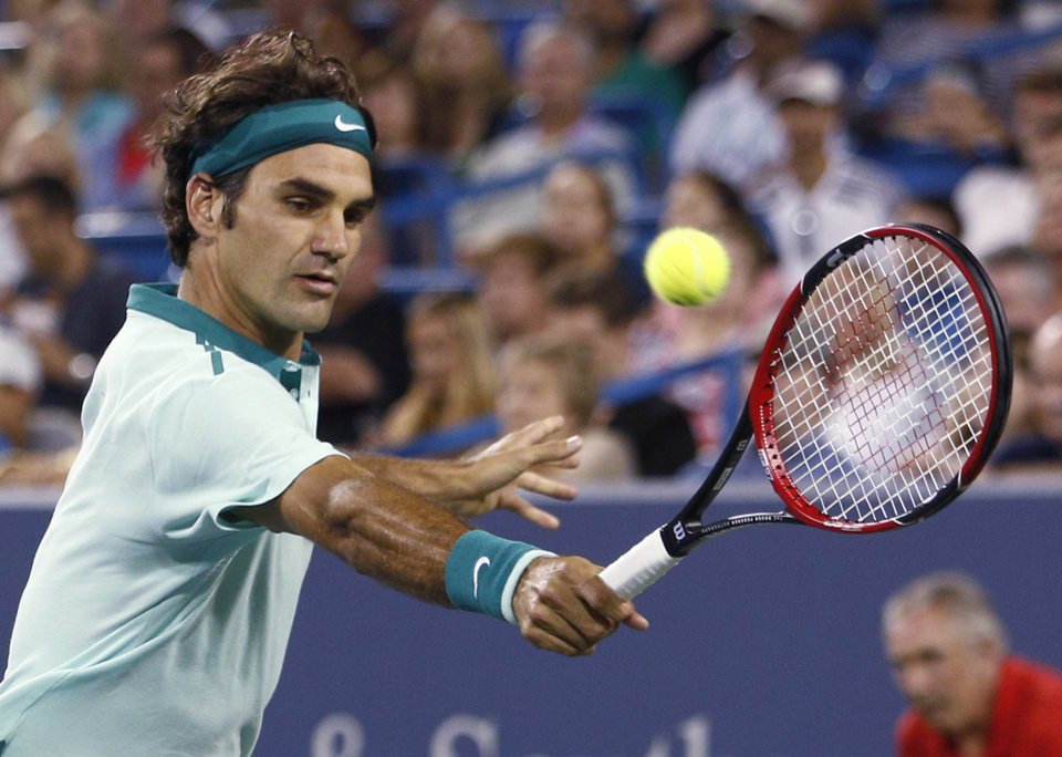 Photo - Roger Federer, from Switzerland, returns a volley to Milos Raonic, from Canada, during a semifinal at the Western & Southern Open tennis tournament, Saturday, Aug. 16, 2014, in Mason, Ohio. Federer won 6-2, 6-3. (AP Photo/David Kohl)