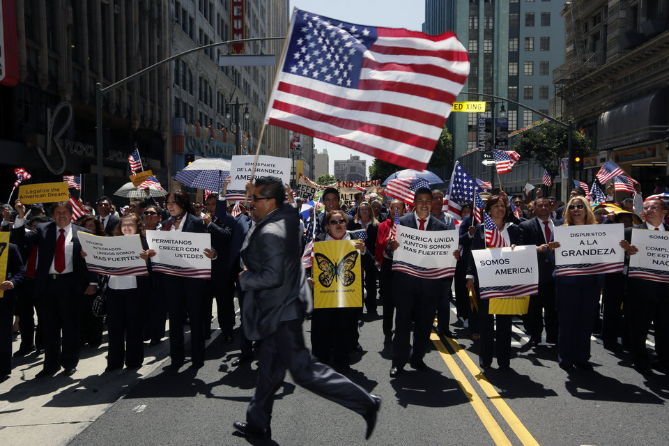 Members of Royal Prestige sales group participate during a May Day rally in downtown Los Angeles on Wednesday, May 1, 2013. In celebration of May Day, people have gathered across the country to rally for various topics including immigration reform. (AP Photo/Damian Dovarganes)
