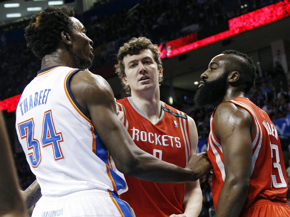 Houston Rockets center Omer Asik (3) gets between Oklahoma City Thunder center Hasheem Thabeet (34) and Rockets guard James Harden (13) in the second quarter of an NBA basketball game in Oklahoma City, Wednesday, Nov. 28, 2012. (AP Photo/Sue Ogrocki) ORG XMIT: OKSO105