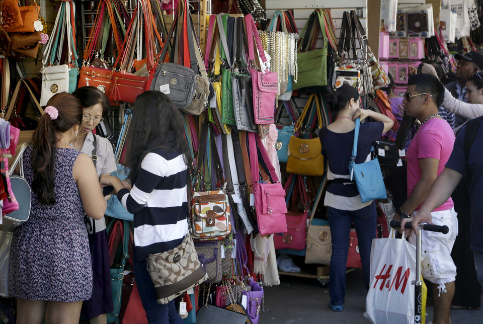 Pedestrians shop for purses and other merchandise on Canal Street in New York, Tuesday, June 4, 2013. Bargain hunters from around the world flock to Manhattan's Chinatown for legally sold bags, jewelry and other accessories bursting onto sidewalks from storefronts along Canal Street. (AP Photo/Seth Wenig)