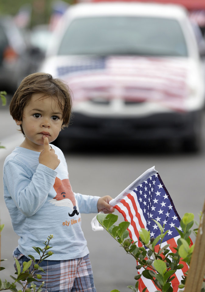 Photo - Cristian Kaemmer, 2, looks on as he attends an immigration demonstration with his Colombian-born mother, in Doral, Fla., Wednesday, May 1, 2013. Demonstrators demanded an overhaul of immigration laws Wednesday in an annual, nationwide ritual that carried a special sense of urgency as Congress considers sweeping legislation that would bring many of the estimated 11 million people living in the U.S. illegally out of the shadows. (AP Photo/Wilfredo Lee)