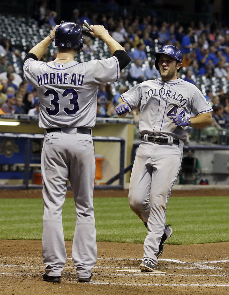 Photo - Colorado Rockies' Ryan Wheeler is congratulated at home by Justin Morneau (33) after hitting a grand slam during the fourth inning of a baseball game against the Milwaukee Brewers Thursday, June 26, 2014, in Milwaukee. (AP Photo/Morry Gash)
