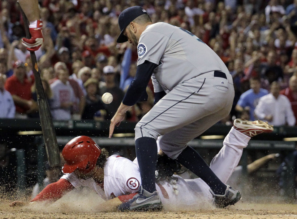 Photo - St. Louis Cardinals' Pete Kozma, bottom, scores the game-winning run on a passed ball as Seattle Mariners relief pitcher Oliver Perez covers home during the 10th inning of a baseball game Friday, Sept. 13, 2013, in St. Louis. (AP Photo/Jeff Roberson)
