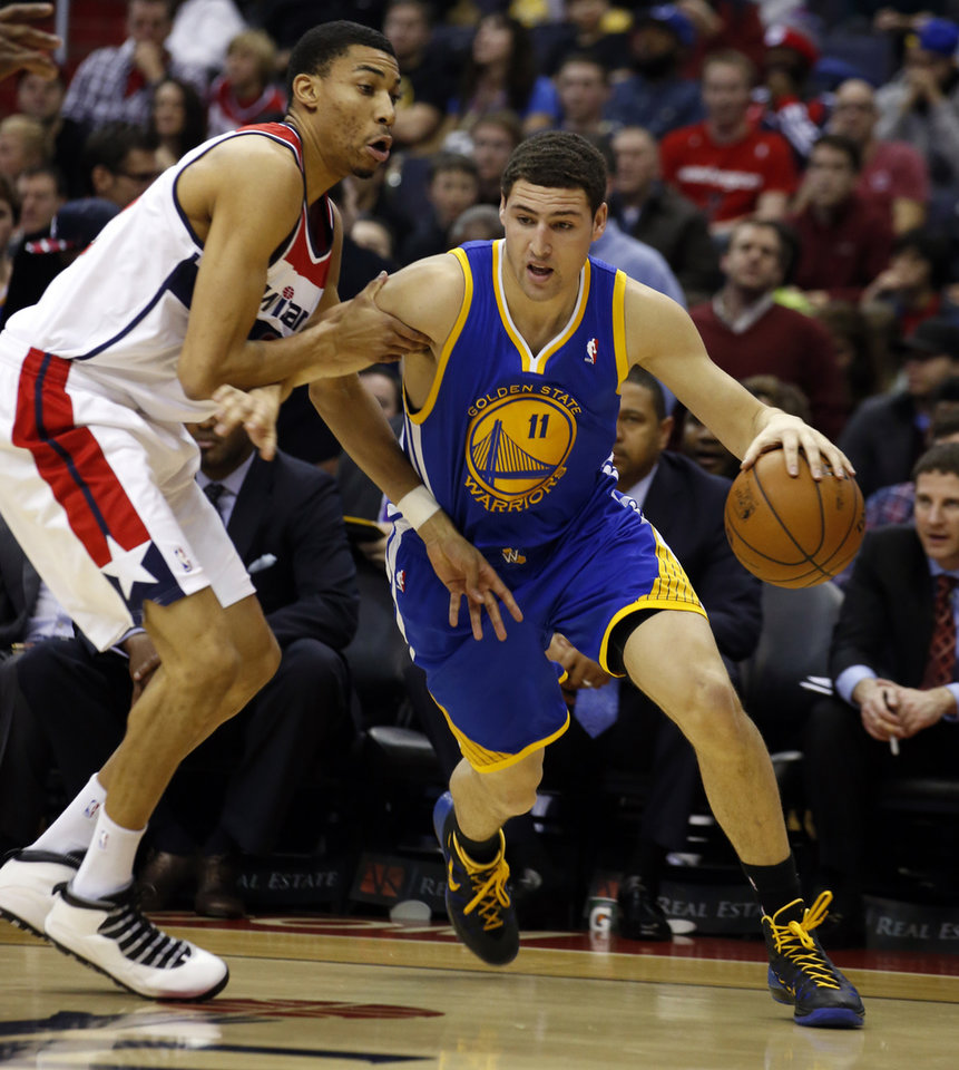 Photo - Golden State Warriors guard Klay Thompson (11) gets past Washington Wizards forward Otto Porter Jr. (22) in the first half of an NBA basketball game on Sunday, Jan. 5, 2014, in Washington. (AP Photo/Alex Brandon)