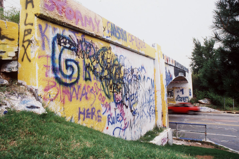Photo - BRIDGES / GRAFFITI BRIDGE / N WESTERN / STREETS / OKC BRIDGES / OKLAHOMA CITY / OKLAHOMA:  Spray-painted with the latest catchy message and setting in all its haphazard, multicolored splendor, the historic graffiti bridge in northwest Oklahoma City is about to come tumbling down.   The bridge, at NW 59 and Western, has had more than its share of close encounters with the wrecking ball. But demolition is set for 10:30 a.m. Saturday, said Paul Brum, city public works department director.  Staff photo by Doug Hoke.  Photo undated and published on 06/26/1991 in The Daily Oklahoman(N).