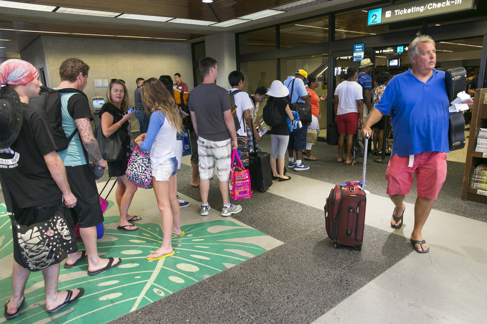 Photo - Crowds line up outside the departures terminal at the Honolulu International Airport in Honolulu on Thursday, Aug. 7, 2014. With Iselle, Hawaii is expected to take its first direct hurricane hit in 22 years. Tracking close behind it is Hurricane Julio. Hawaiian Airlines announced Thursday they are waiving change fees for passengers trying to leave before the hurricanes hit the islands. (AP Photo/Marco Garcia)