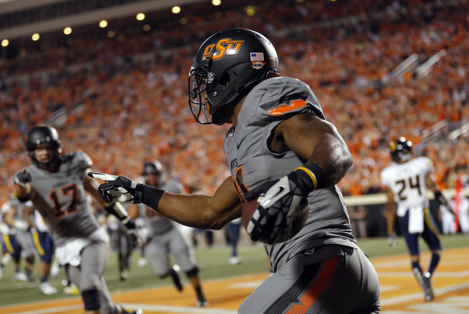 Photo - Oklahoma State's Jeremy Smith (31) celebrates a touchdown during a college football game between Oklahoma State University (OSU) and the West Virginia University at Boone Pickens Stadium in Stillwater, Okla., Saturday, Nov. 10, 2012. Photo by Sarah Phipps, The Oklahoman