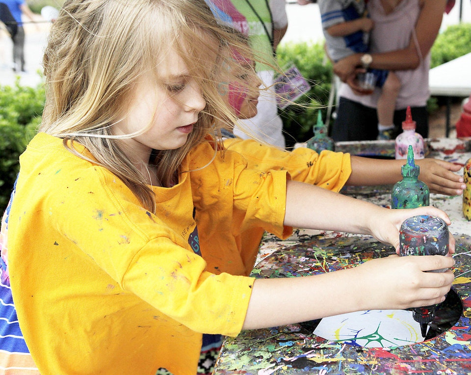 Photo - Reagan Jones, 8, makes art on a spinning canvas booth for children at the Paseo Arts Festival in Oklahoma City on May 25, 2013. Photo by KT King, The Oklahoman