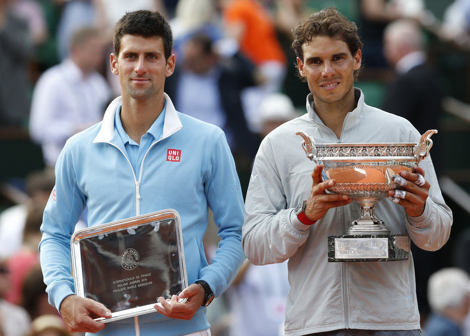 Photo - Spain's Rafael Nadal, right, holds the trophy after winning the final of the French Open tennis tournament against Serbia's Novak Djokovic, left, at the Roland Garros stadium, in Paris, France, Sunday, June 8, 2014. Nadal won in four sets 3-6, 7-5, 6-2, 6-4. (AP Photo/Darko Vojinovic)