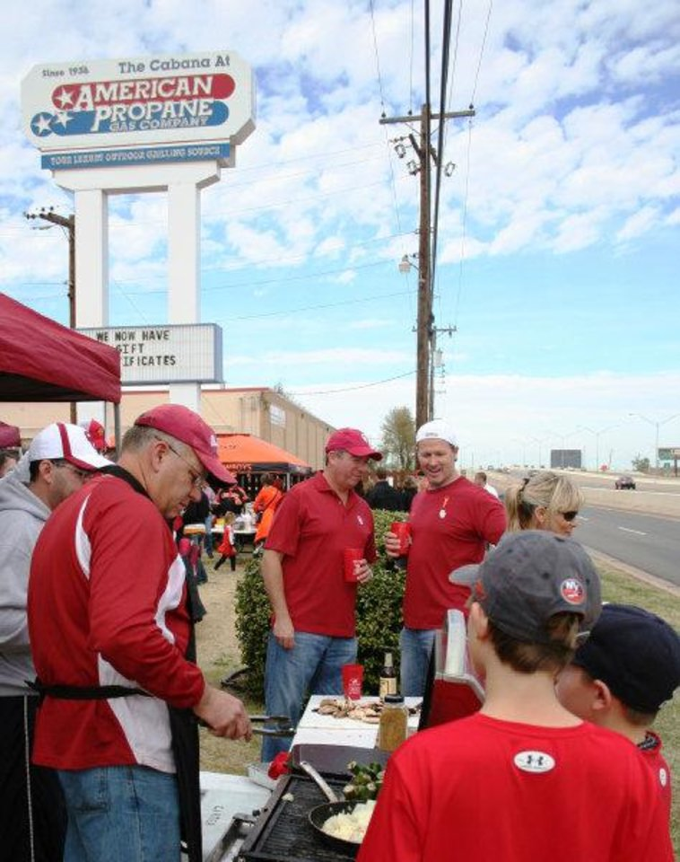 Sooner fans gather around the grill with Steve Carter of the Two Docs tailgating during the Bedlam Tailgating Showdown. <strong>DAVE CATHEY - THE OKLAHOMAN</strong>