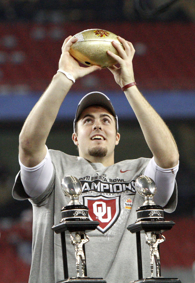 Photo - Oklahoma's Landry Jones (12) holds part of the trophy after the Fiesta Bowl college football game between the University of Oklahoma Sooners and the University of Connecticut Huskies in Glendale, Ariz., at the University of Phoenix Stadium on Saturday, Jan. 1, 2011.  Photo by Bryan Terry, The Oklahoman